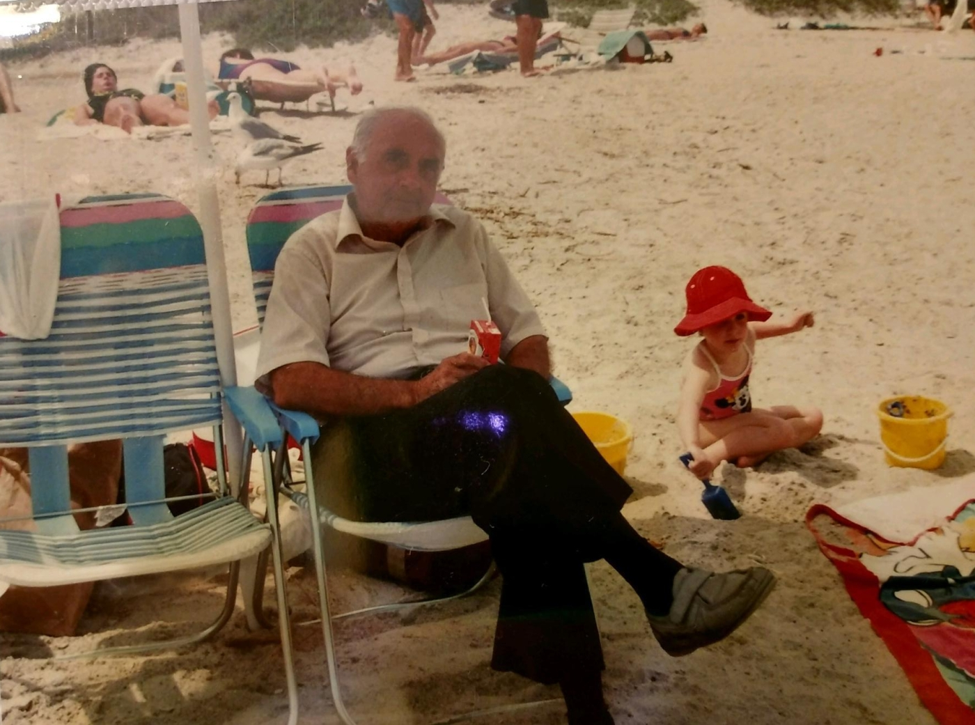 Grandfather sits in a beach chair with little girl playing beside him in the sand