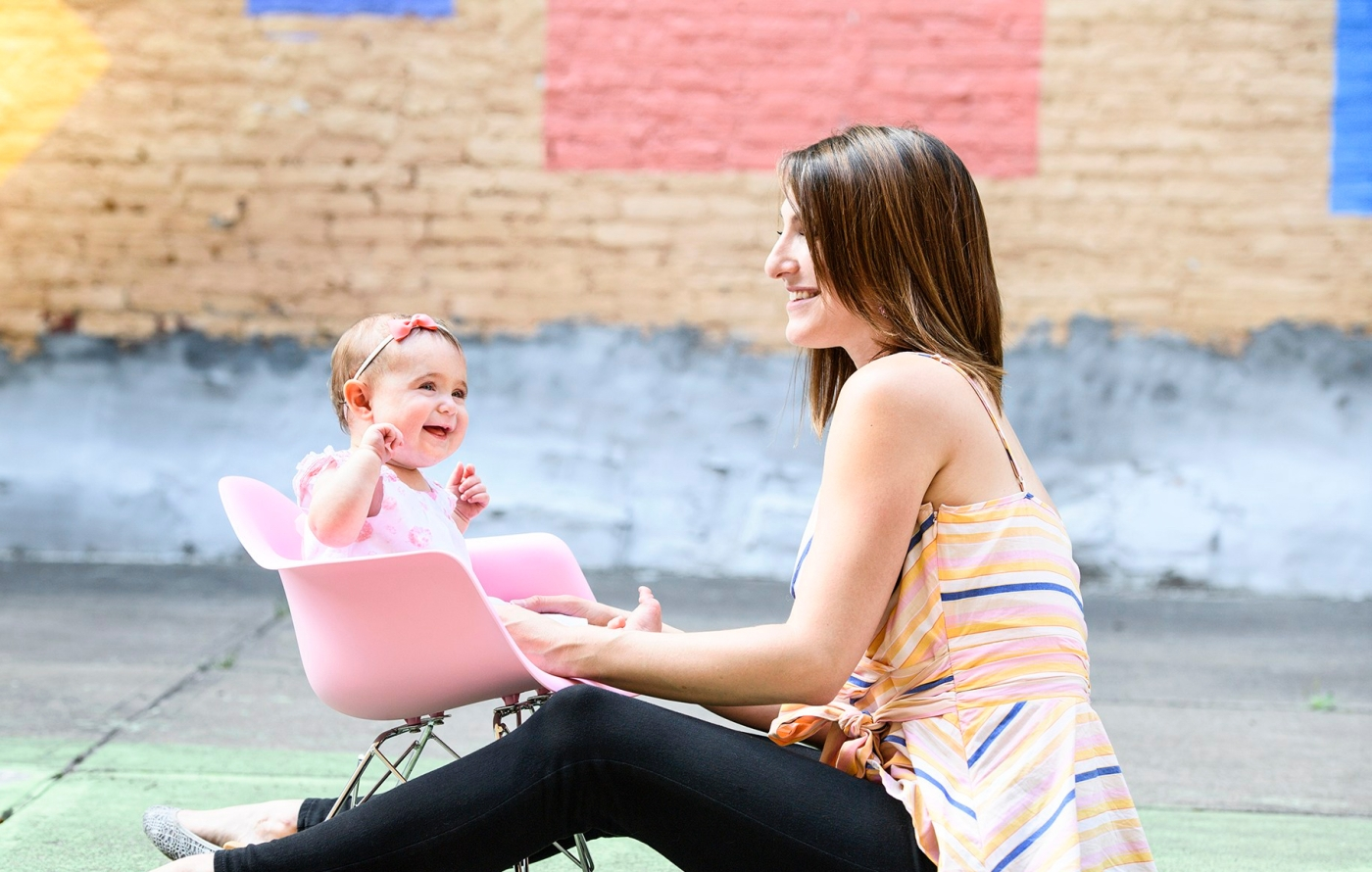 Mother and baby girl facing each other and laughing