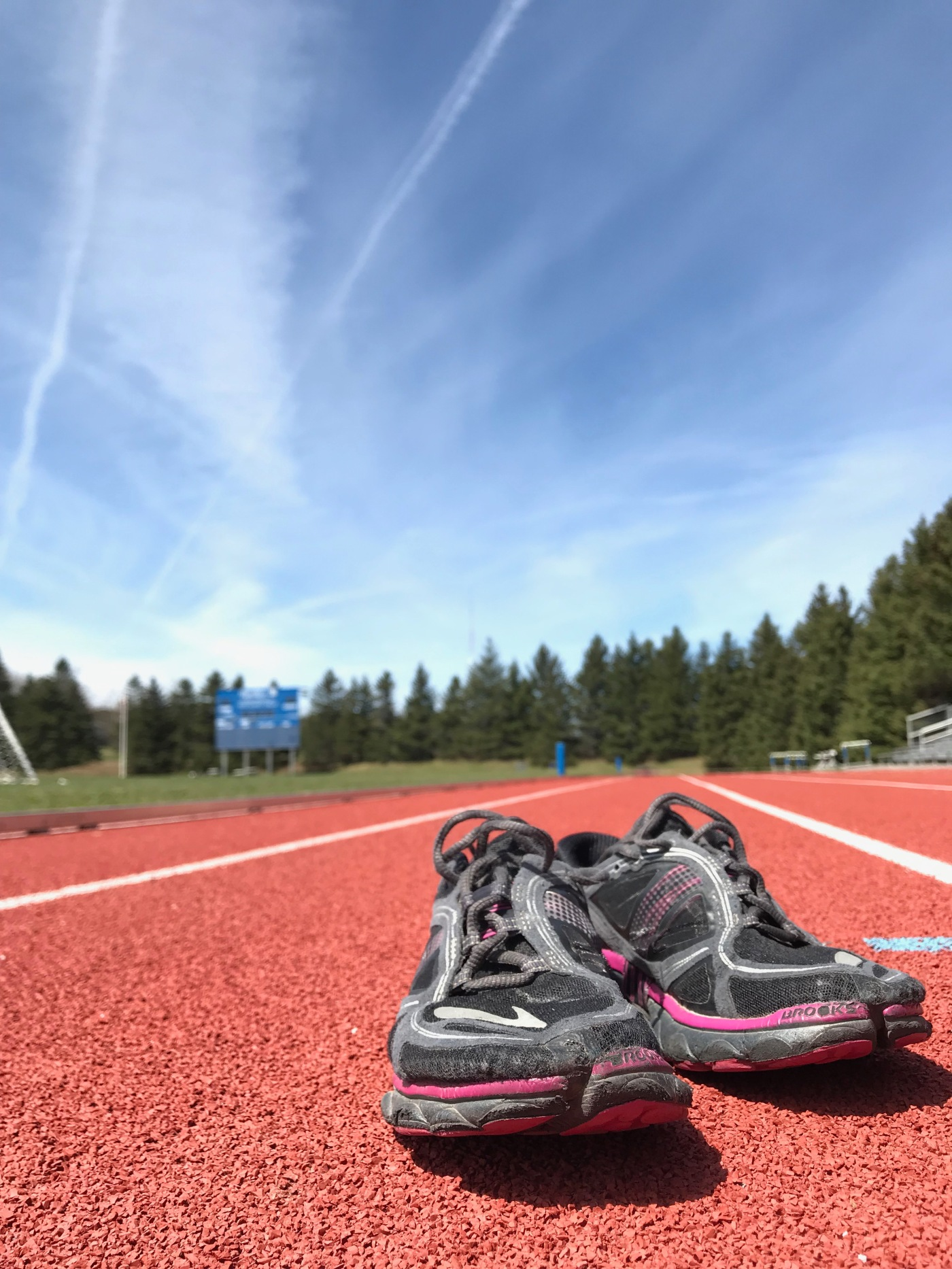 closeup of two sneakers on a red track surface, blue sky with pine trees in the distance